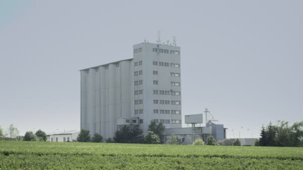 Grain concrete silo building in flattened landscape, big seed elevator. Footage of agriculture countryside, farming, husbandry in plain, flat land