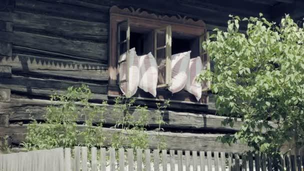 Otevřít staré okno s polštáři. Vyvětrání spací deky. Středověké dřevěné vesnice v údolí. Malebné letní krajina na dovolené