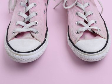 pair of old worn pink sneakers with white laces on a pink background, close up