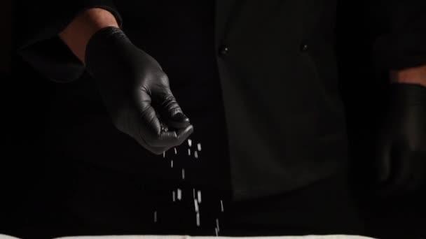 Schwarze Latex-Handschuhe streuen weißes grobes Salz auf schwarzem Hintergrund