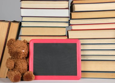 brown teddy bear and empty black board in red frame on the backg