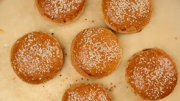 pečené sezamové buchty na hnědém pergamenovém papíru, přísada na hamburger, pohled shora