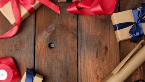 Geschenke in braunem Kraftpapier verpackt und mit Seidenband auf einem braunen Holztisch gebunden, weibliche Hände legen die Schachtel in die Mitte, Ansicht von oben
