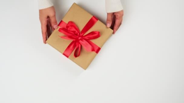 két női kéz tesz egy fehér asztalra egy négyzet alakú dobozt barna kraft papírba, az ajándék piros selyem szalaggal van megkötve, felülnézetből
