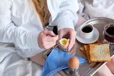 Breakfast in bed in hotel. Redhead gird after taking shower has a breakfast in bed in hotel room.