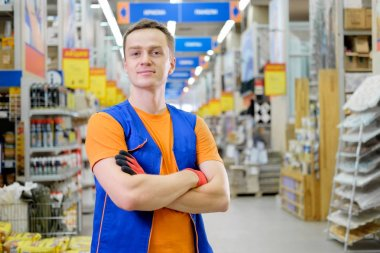 Young salesman standing at construction super store. Portrait of attractive confident working man in uniform on his workplace in building store. People at work concept.