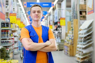 Young handsome salesman standing at construction super store. Portrait of attractive confident working man in uniform on his workplace in building store. People at work concept. Copyspace.