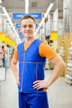 Young salesman standing at construction super store. Portrait of attractive cheerful confident working man in uniform on his workplace in building store. People at work concept.