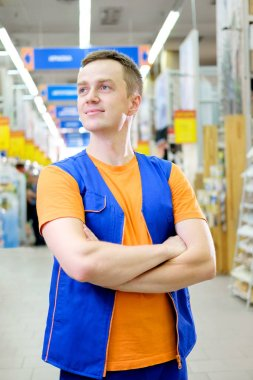 Young handsome salesman standing at construction super store. Portrait of attractive cheerful confident working man in uniform on his workplace in building store. People at work concept.