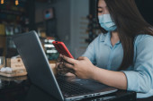 Asian woman wearing a mask uses a smartphone in a coffee shop.