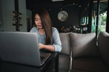 A female Asian office worker of Thai descent is typing and working with notebooks in a coffee shop during the day. She was wearing a blue shirt