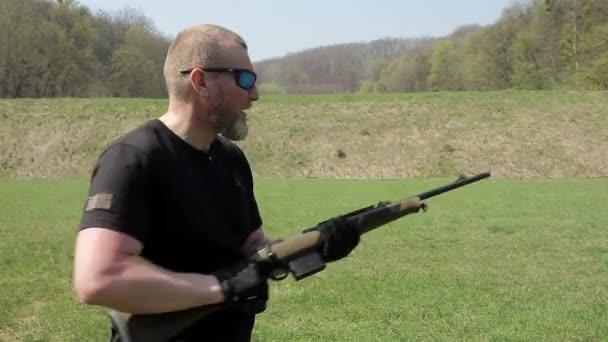 Egy ember karabély pisztolyt. Az ember a szemüveg célokat a karabély