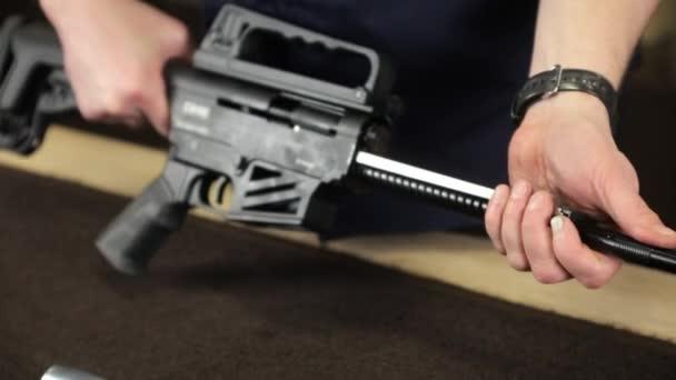 Männerhände zerlegen das Gewehr