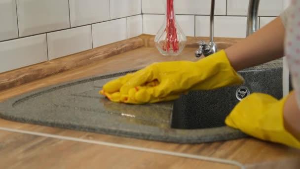 Reinigung des Spülbeckens. Frau in gelben Gummihandschuhen wäscht eine Küchenspüle. Frau in gelben Gummihandschuhen wäscht eine Spüle.