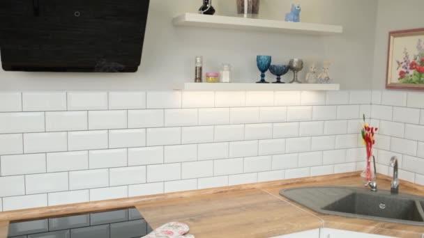 Skandinávská bílá kuchyně s dřevěnými policemi, minimalistickým designem nebo interiérem