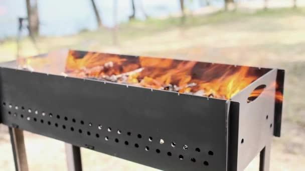 Gyönyörű vörös tűz vágott fa, sötét szürke fekete szén belül fém brazier. Égő fa a brazilban, sárga tűzben. Lángok tűz előkészítése főzés barbecue. Brazília a természetben bbq.