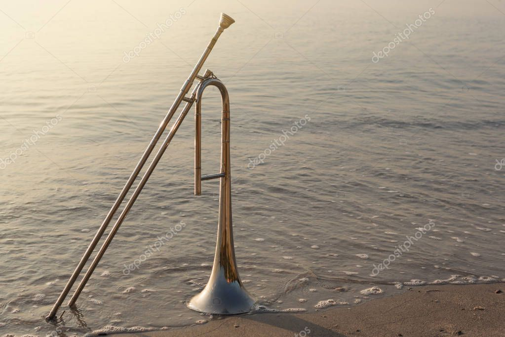 concept of music and romance, wind instrument trumpet stands on the sand, the seashore, sunrise beautiful lighting