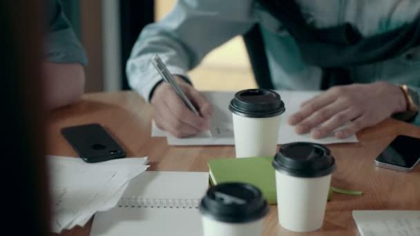 Mužské ruce členů týmu zapisování poznámek na papír práci plán pomocí pera týmu setkání a debata