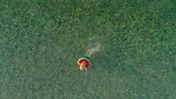 Hochwinkel kleiner europäischer Junge schwimmt mit Rettungsring im Meer und genießt den Urlaub