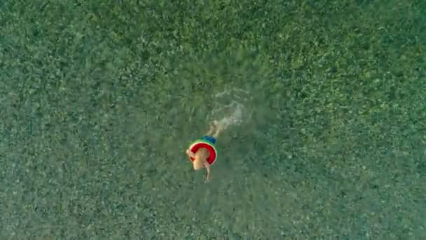 High angle little European boy swimming in sea using lifebuoy enjoying vacation