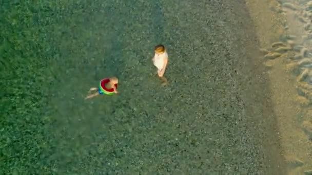Top view caring mother helping little son swimming using lifebuoy in clear sea water