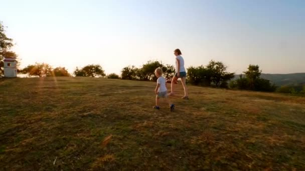 Active family young mother and happy little son walking on mountain hiking hilly terrain at sunset