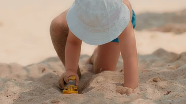 Baby boy wearing hat and bathing shorts playing with toy tractor or excavator in sandbox on beach
