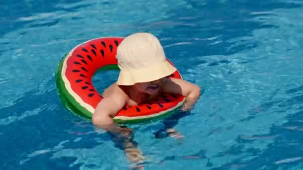 Smiling little European boy wearing hat floating in outdoor swimming pool using lifebuoy