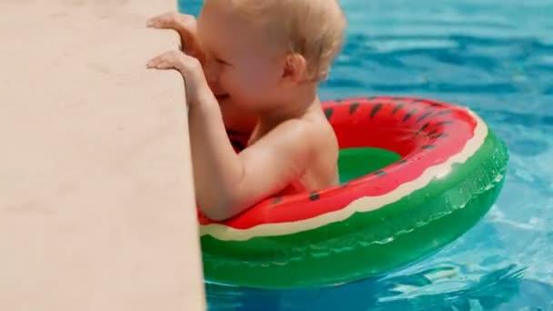 kleiner europäischer Junge lächelt und hat Spaß, wenn er sich mit Rettungsring an den Rand des Freibades lehnt