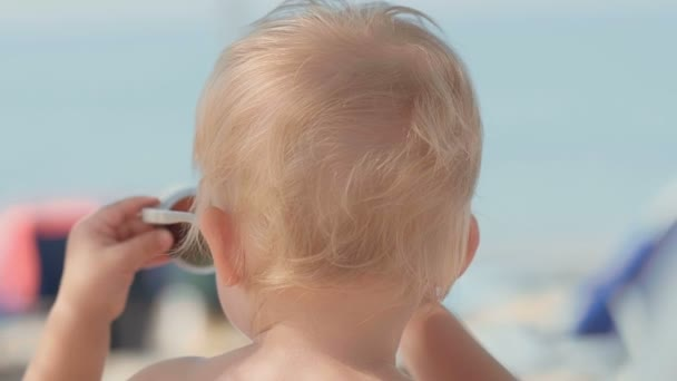Close-up smiling European little boy wearing mother female sunglasses looking around on beach happy child enjoying summer vacation trying and contemplating through big sunglasses