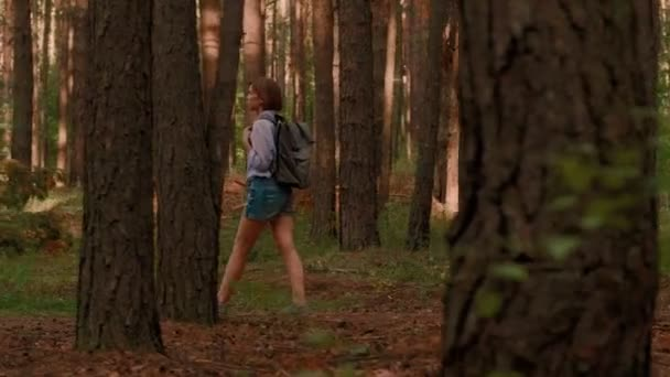 Hipster backpack women enjoying walking in forest surrounded by thick trunk trekking shot