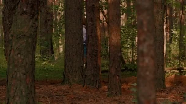 Traveler backpack women enjoying walking in forest surrounded by thick trunk trekking shot