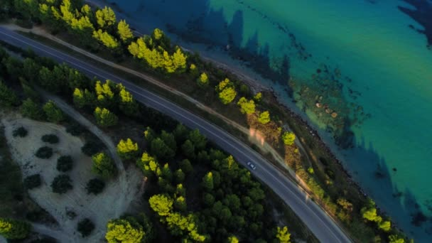 View from above car moving on asphalt road surrounded by sea beach coastline and green dense forest in Greece