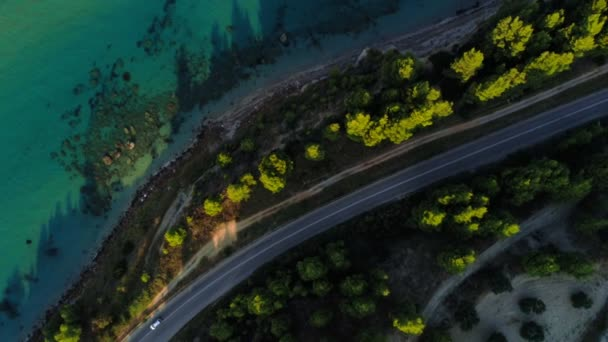 Aerial shot flying over amazing natural landscape asphalt road with moving car along sea beach in Greece