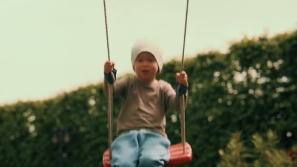Smiling baby boy swinging on swing having good time outdoor slow motion