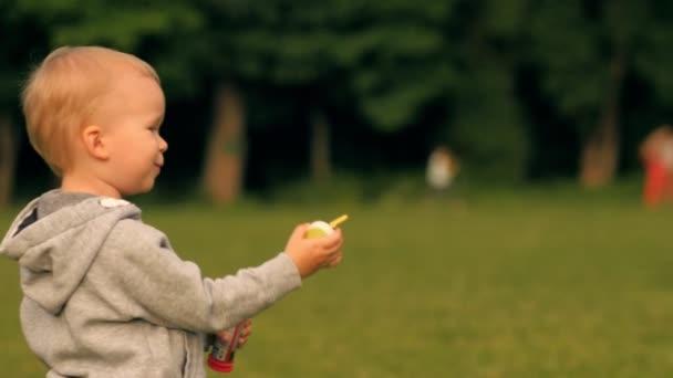 Boldog kis bébi gyerek szórakozik fúj szappanbuborék a szabadtéri nyári parkban élvező gyermekkori