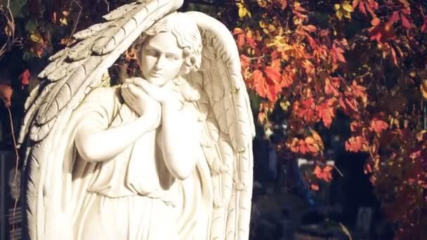 Fehér szobor egy angyal, a háttérben az erdő