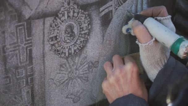 die Hand des Graveurs zeichnet auf Stein