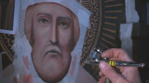 die Hand des Graveurs zeichnet die Airbrush der Nikolaus des Wundertäters. Nahaufnahme
