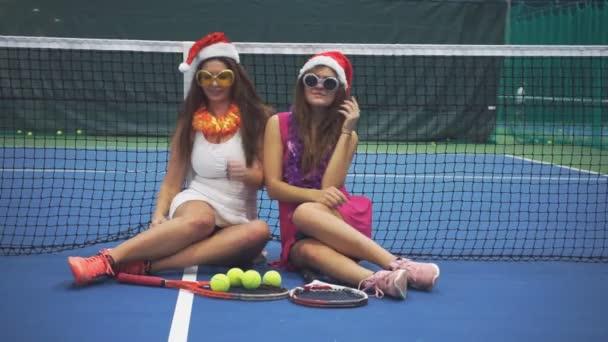 Dvě dívky sportovci sedět na tenisový kurt a představují