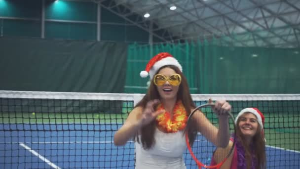 Two pretty girls sit on the tennis court in the New Years accessories