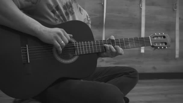 Muž sedí a hraje na akustickou kytaru. Closeup