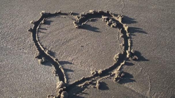 Herzsymbol auf Sand von Hand gezeichnet