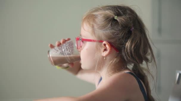 dívka pije kakao ze skla