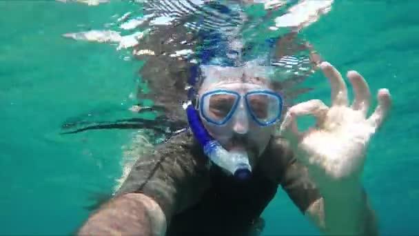 Taucher taucht unter Wasser und gibt Okay-Zeichen