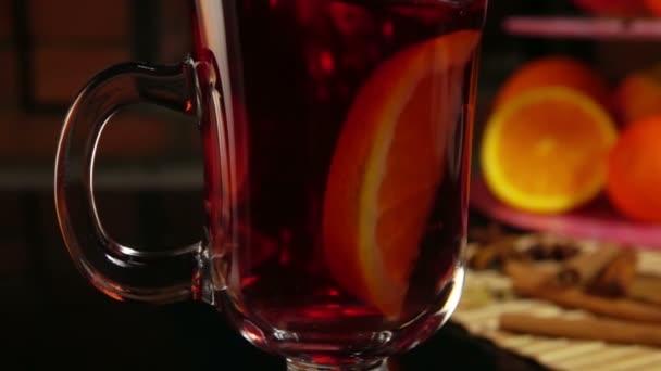 Orangenscheibe fällt in einen schönen Becher Glühwein