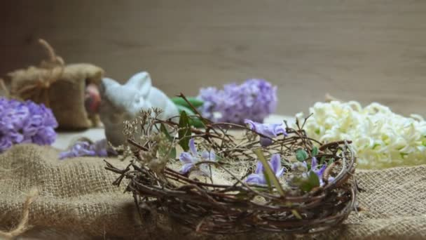 Childs hand puts colored egg in in the Easter nest
