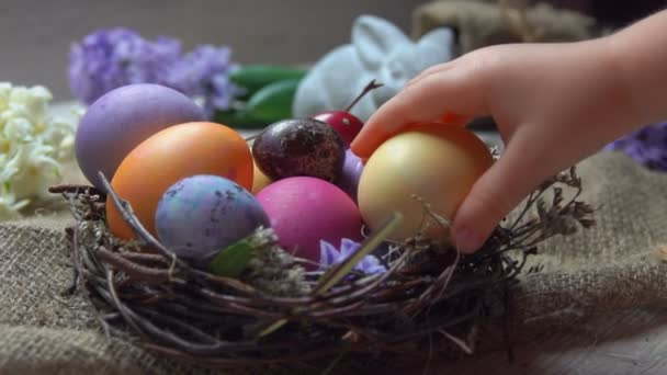 Childs hand takes and lays festive colored egg