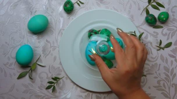 Ruční odebere skleněnou kopulí z desky s zelenou velikonoční vajíčka