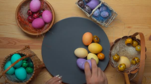 Womans hand puts colored easter eggs